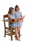 picture of illiteracy  - Two little girls reading together at a wooden school desk - JPG