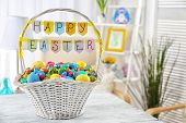 Easter basket with colorful eggs on wooden table poster