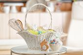 Easter basket with gifts and painted eggs on light blurred background poster