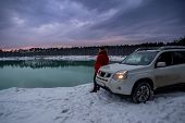 Man Near Suv Car At Winter Time. Lake With Forest On Background. Active Lifestyle poster