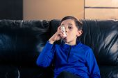 8 Year Old Boy Wearing Sportive Clothing Using An Asthma Inhaler Sitting In Sofa. Concepts : Health, poster