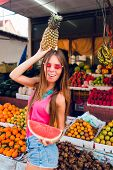 Filled With Joy Girl Having Fun On Market On Tropical Fruits Background. She Holds Ananas On Head An poster