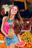 Filled With Joy Summer Girl Having Fun On Market On Tropical Fruits Background. She Holds Ananas, Sl poster