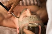 Closeup of beautician hands holding jar and applying mud mask on face of mature woman with brush. Be poster
