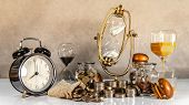 Sand Running Through The Shape Of Hourglass With Coins, Money Jars And Clock On The Table. Time Inve poster
