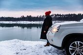 Young Adult Woman In Winter Clothes With Red Hat With Bubo Standing Near Suv Car At River Side With  poster