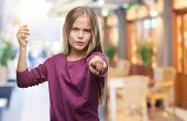 Young beautiful girl holding blank paper card over isolated background pointing with finger to the c poster