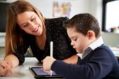 Close up of young female teacher sitting at desk with a Down syndrome schoolboy using a tablet compu poster