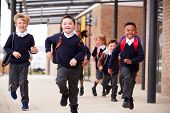 Excited primary school kids, wearing school uniforms and backpacks, running on a walkway outside the poster