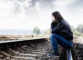 stock photo of loneliness  - Sad teenager sitting on the tracks looking into the distance and thinking - JPG