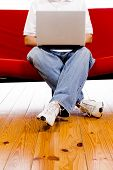 picture of futon  - A man sitting on a red couch working on a laptop computer on a whtie background - JPG