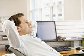 Young businessman reclining in office chair at desk