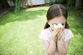 stock photo of blowing nose  - Young girl blowing nose with tissue paper in backyard - JPG