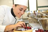 picture of confectioners  - Cheerful girl at training school making cake - JPG