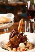 picture of lamb shanks  - Restaurant table with lamb shank served with onion - JPG