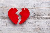 stock photo of heartbreak  - Broken heart hanging on rope - JPG