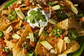 stock photo of nachos  - Homemade Unhealthy Nachos with Cheese Sour Cream and Vegetables - JPG