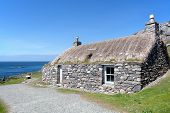 Traditional Scottish Black House On The Edge Of Atlantic Ocean