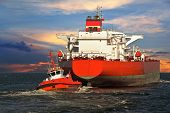 picture of towing  - Tug boat towing a tanker ship at sea - JPG
