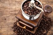stock photo of wood  - Close up fresh coffee bean in coffee bean grinder next to coffee bean on wooden table top - JPG