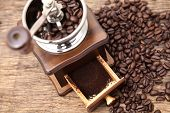 foto of coffee grounds  - Vintage coffee bean grinder and fresh ground coffee on wooden top next coffee beans - JPG