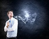 foto of fumes  - Young handsome businessman in fumes smoking pipe - JPG