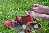 stock photo of breather  - Barefoot woman with red shoes relaxing on a meadow - JPG
