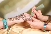 stock photo of mehendi  - Process of applying Mehndi on female hand - JPG