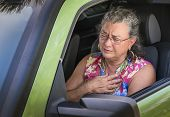pic of blood drive  - Sweaty hot senior woman winces with stress and chest pain while driving car - JPG