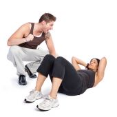 stock photo of personal trainer  - A woman doing situps with her personal trainer - JPG