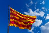 picture of flag pole  - Catalan flag with pole blowing in the wind on blue sky with clouds - JPG