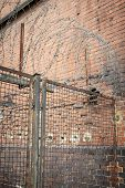 picture of old stone fence  - barb wire on an old fence with red brick wall - JPG