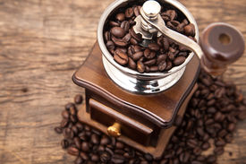 foto of traditional  - Close up fresh coffee bean in coffee bean grinder next to coffee bean on wooden table top - JPG