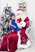 picture of saint-nicolas  - little girl in a beautiful blue dress sits on a lap at Saint Nicolas about a New Year tree - JPG