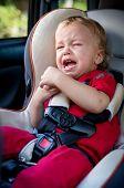 stock photo of crying boy  - crying baby boy in car seat saving time - JPG