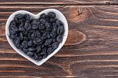 stock photo of barberry  - barberry spice in a bowl in the form of heart on a wooden background - JPG