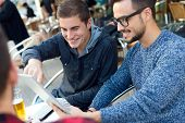 stock photo of entrepreneur  - Outdoor portrait of young entrepreneurs working at coffee bar - JPG