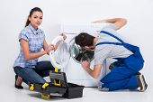 picture of washing machine  - Repairman is repairing a washing machine for housewife - JPG
