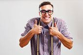 stock photo of stereotype  - Happy nerdy man is showing thumbs up - JPG