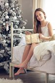 pic of preteen  - Preteen child girl wake up in her bed near decorated Christmas tree in beautiful hotel room in the holiday morning - JPG