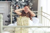 image of preteen  - Preteen child girl wake up in her bed near decorated Christmas tree in beautiful hotel room in the holiday morning - JPG