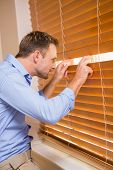 picture of blind man  - Curious man looking through the blinds at home - JPG