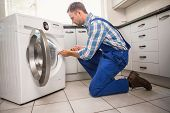 stock photo of handyman  - Handyman fixing a washing machine in the kitchen - JPG