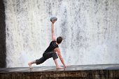 stock photo of elliptical  - Fit white man exercising with elliptical ball  at waterfall  - JPG