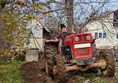 stock photo of plowing  - Senior farmer on an old red tractor plowing his garden in the backyard  - JPG