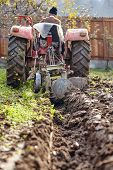 picture of plow  - Senior farmer on an old red tractor plowing his garden in the backyard - JPG