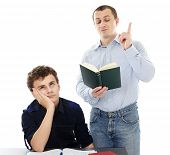 picture of boredom  - Teenage student displaying boredom sitting at his desk while his father is lecturing - JPG
