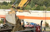 stock photo of track-hoe  - Tracked excavator loading a dump truck at a large construction site removing a hill during an airport runway expansion project - JPG