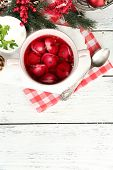 image of christmas meal  - Traditional polish clear red borscht with dumplings and Christmas decorations on wooden table background - JPG