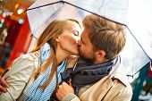 pic of amor  - Amorous couple kissing under umbrella in urban environment - JPG